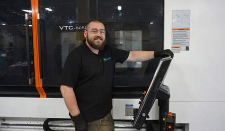An employee in front of the new machine.
